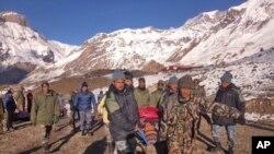 Para tentara Nepal mengangkat seorang korban salju longsor dengan tandu, sebelum diterbangkan dengan helikopter di area Thorong La, Nepal (15/10).
