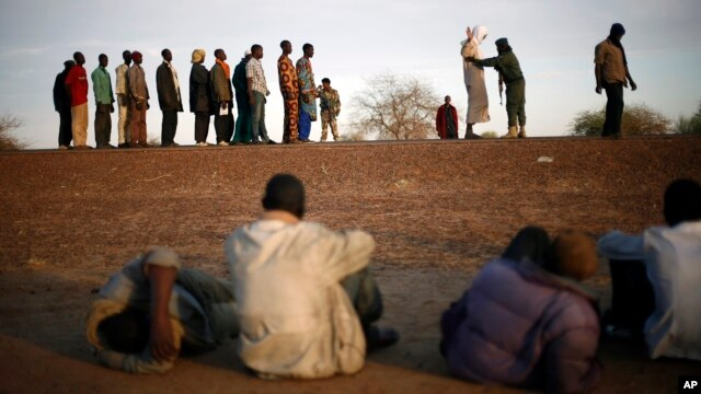 Travelers driving from Niamey, Niger, lining up to be searched at the entrance of Gao, northern Mali, Feb. 12, 2013.