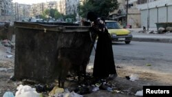 FILE - A woman is seen searching for food in a garbage container in Aleppo, Syria, July 31, 2013.