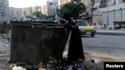 Hình tư liệu - Một người phụ nữ tìm kiếm thực phẩm trong thùng rác ở Aleppo, Syria, ngày 31 tháng 7 năm 2013.