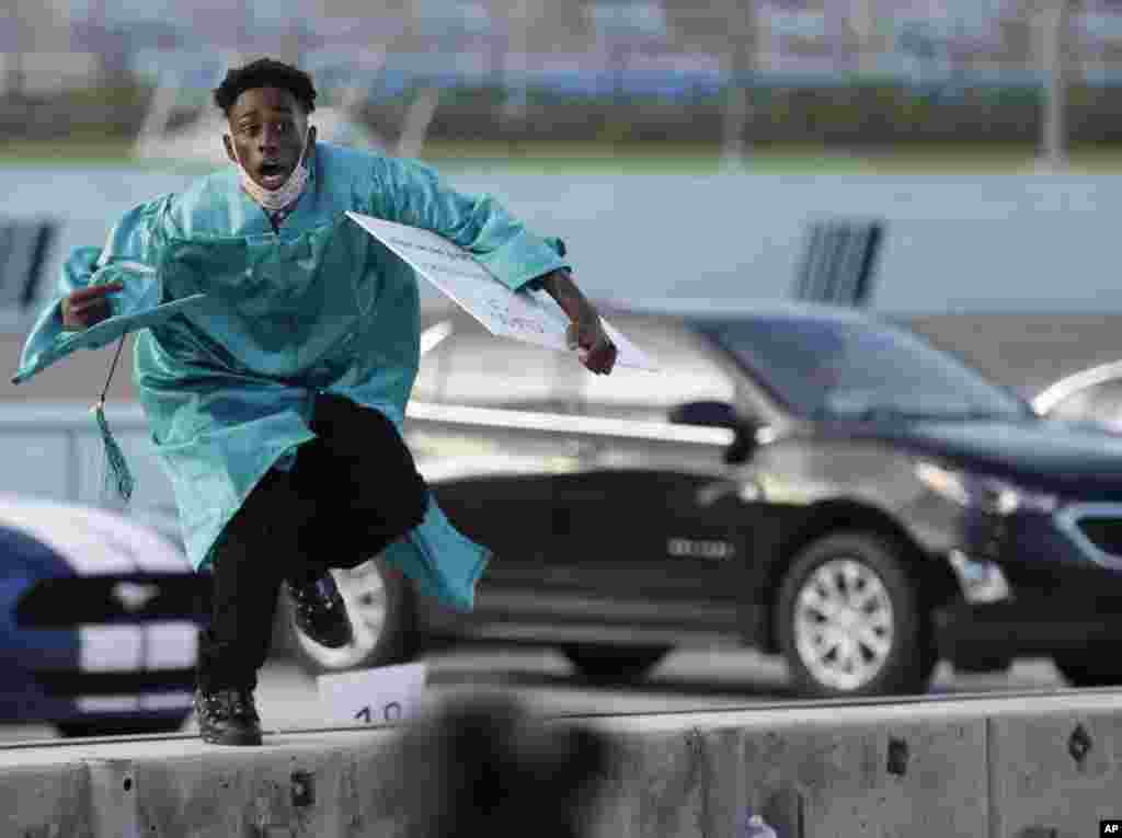 Richardson Fremond leaps over a wall as he runs to collect an award during a graduation ceremony for the senior class of Chambers High School at Homestead-Miami Speedway, in Homestead, Fla., June 23, 2020.