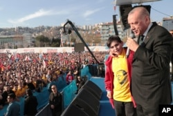 Turkey's President Recep Tayyip Erdogan reacts with a boy as he addresses the supporters of his ruling Justice and Development Party during a rally in Kocaeli, Turkey, March 19, 2019. Ignoring widespread criticism, Erdogan on Tuesday again showed excerpts of a video taken by the attacker who killed 50 people in mosques in New Zealand, to denounce rising hatred and prejudice against Islam.