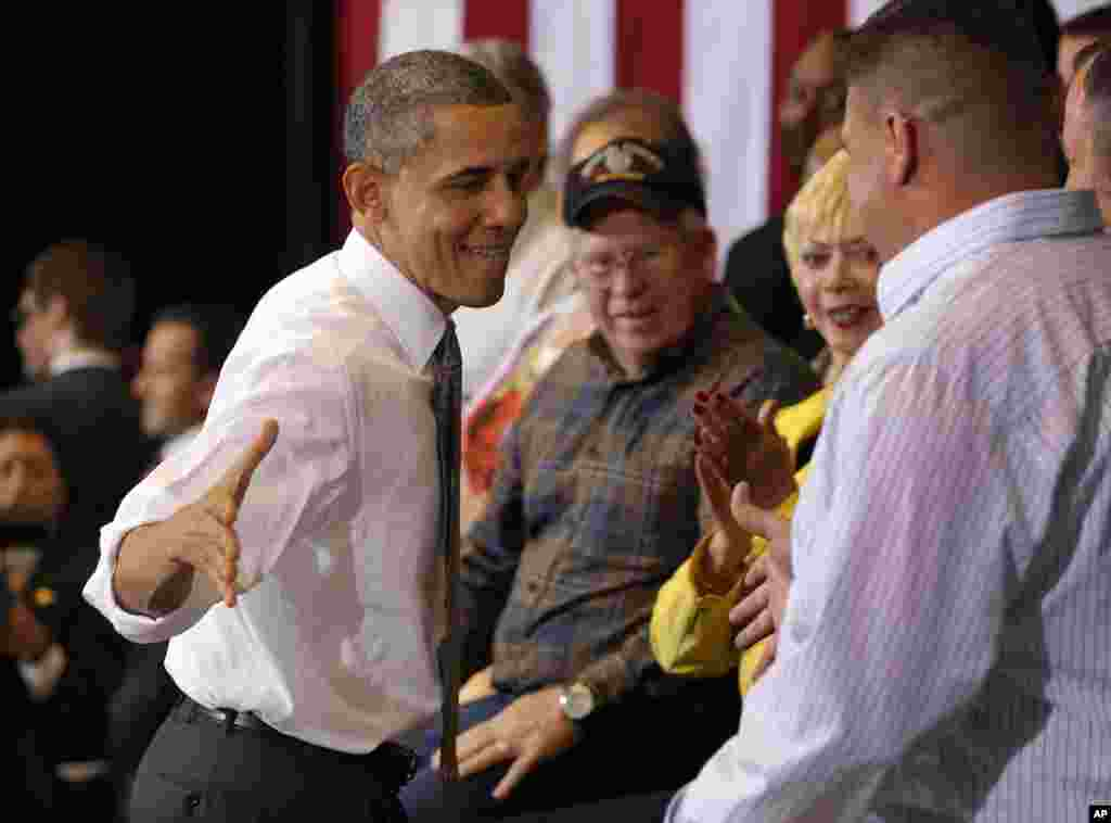 President Barack Obama reaches out to shake hands with Lorain County Community College student Bronson Harwood after speaking at the college in Elyria, Ohio, April 18, 2012.