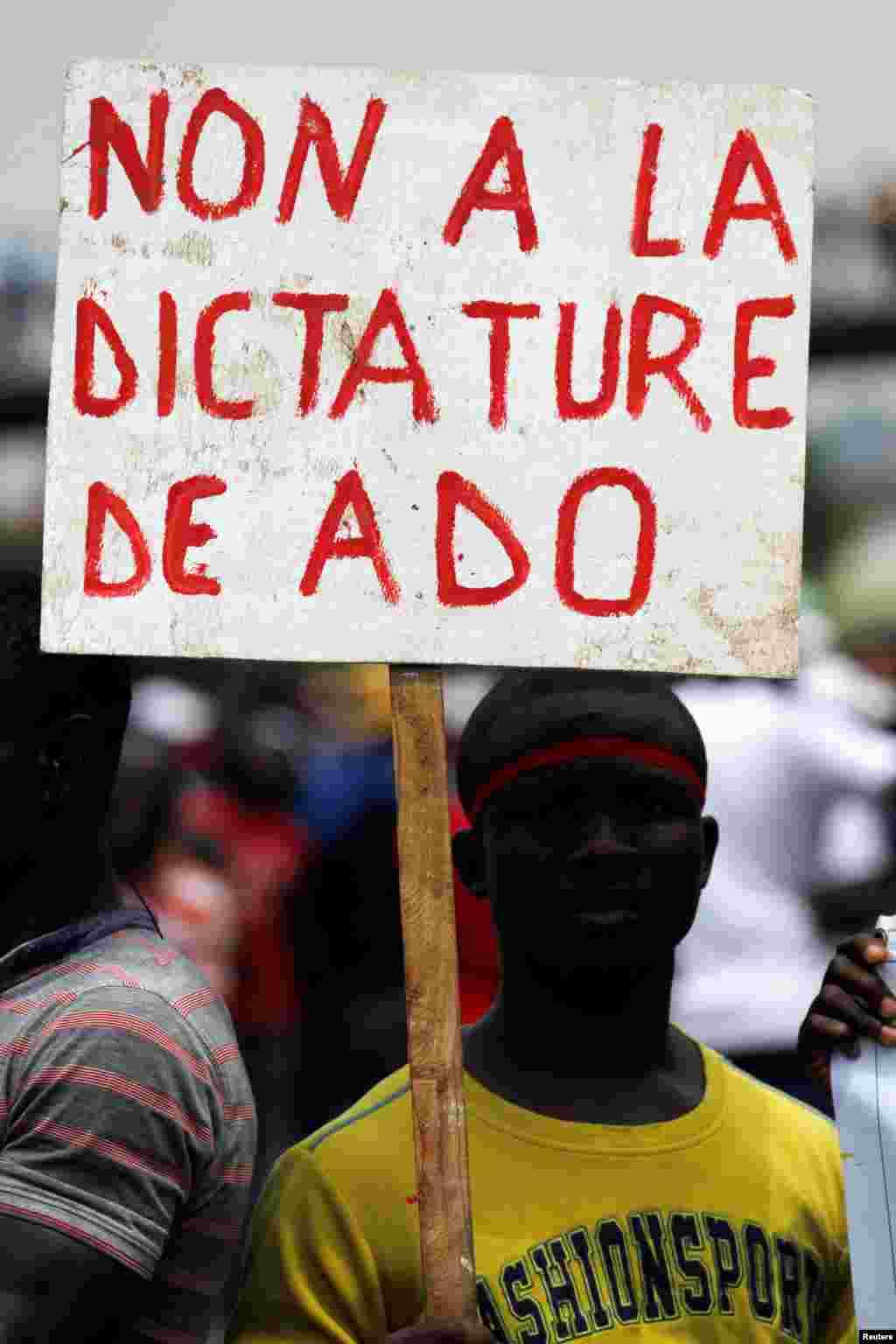 Un manifestant tient une pancarte alors que les gens protestent avant le référendum sur une nouvelle constitution, à Abidjan, le 28 Octobre 2016.