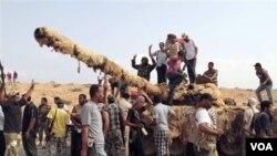Pejuang revolusi merayakan kemenangan mereka setelah menguasai sebuah tank dari kubu pro-Gaddafi di Sirte, Libya (20/9).