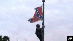 Bree Newsome dari Charlotte, North Carolina, memanjat tiang bendera untuk menurunkan bendera Konfederasi di monumen Konfederasi di Columbia, South Carolina (27/6). (AP/Bruce Smith)