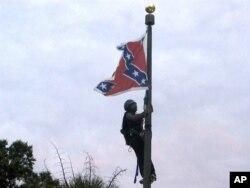 Бри Њусом од Шарлот, Северна Каролина, се обидува да го симне знамето од јарболот на Споменикот на Силите на Конфедерацијата пред Државниот дом на Јужна Каролина во градот Колумбија