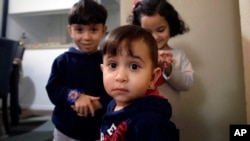 Syrian refugee Mohammad word al Jaddou, front, stands in front of his siblings twins Maria, right, and Hasan at their apartment in Dallas.