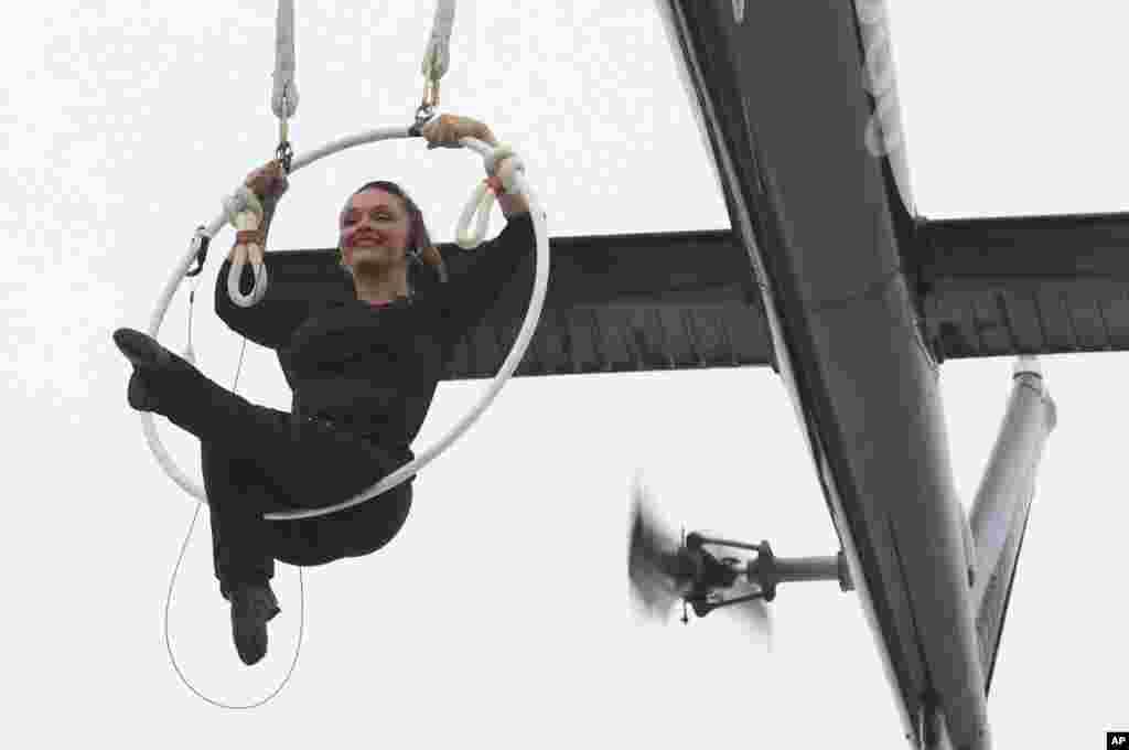 نماش حرکات آکروباتیک توسط دختر آکروبات باز در حالی که معلق از هلیکوپتری بر فراز آبشار نیاگارا است.