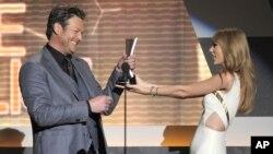 Taylor Swift, derecha, entrega el premio de Vocalista del año a Blake Shelton en 2012. Ambos están nuevamente entre los nominados.