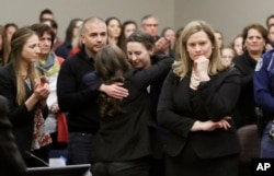 Former gymnast Rachael Denhollander, center, is hugged after giving her victim impact statement during the seventh day of Larry Nassar's sentencing hearing Wednesday, Jan. 24, 2018, in Lansing, Michigan.