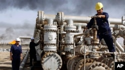 FILE - Iraqi workers at the Rumaila oil refinery, near Basra, 340 miles (550 kilometers) southeast of Baghdad, Iraq.