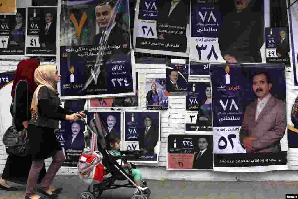 People walk past campaign posters for Iraq's parliamentary elections in Sulaimaniya, April 28, 2014.