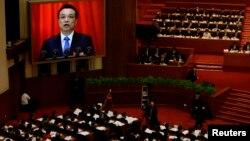 Thủ tướng Trung Quốc Lý Khắc Cường, trên màn hình, đọc báo cáo của chính phủ trong buổi lễ khai mạc Đại hội Đại biểu Nhân dân Toàn quốc tại Đại lễ đường Nhân dân ở Bắc Kinh, 5/3/14