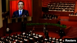 China's Premier Li Keqiang is seen on a screen delivering the government work report during the opening ceremony of the National People's Congress (NPC) at the Great Hall of the People in Beijing, March 5, 2014.