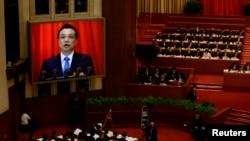 中国人大在北京大会堂开幕,现场大屏幕上显示李克强做政府报告。2014年3月5日