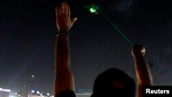 Un hombre egipcio apunta con un laser a un helicóptero. En un hecho similar, un hombre puertorriqueño fue arrestado por el FBI.