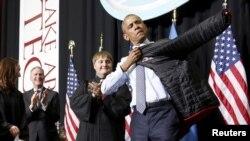 Presiden AS Barack Obama menerima jaket almamater dari Lake Area Technical Institute di Watertown, South Dakota (8/5) usai memberikan pidato kelulusan. (Reuters/Jonathan Ernst)