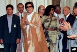 FILE - Libyan leader Muammar Gaddafi (C) arrives at Cairo university for a meeting with university professors, May 27, 1996.