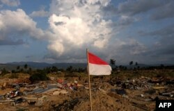 An Indonesian flag flies over the flattened village of Petopo in Palu, Indonesia's Central Sulawesi