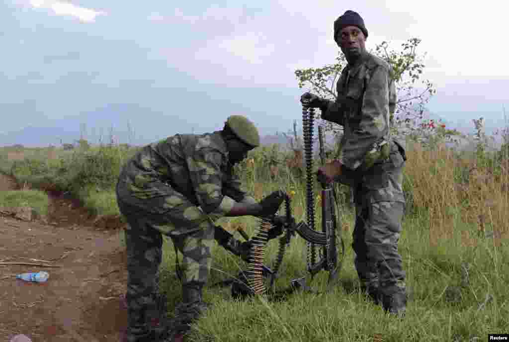 Soldiers from the Democratic Republic of Congo check their weapons near the town of Kibumba at its border with Rwanda after fighting broke out, June 11, 2014.