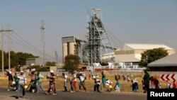 Members of the mining community carry donated food parcels at the Khomanani mine in Rustenburg, South Africa, May 28, 2014.