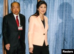 Thailand's PM Yingluck Shinawatra (R) and Deputy PM Surapong Tovichakchaikul arrive before a meeting with the Election Commission at the Royal Thai Air Force Academy in Bangkok, Apr. 30, 2014.