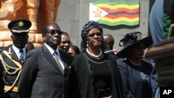 Zimbabwean President Robert Mugabe and his wife Grace attend the burial of Solomon Mujuru, the country's first defense chief and husband of Vice President Joyce Mujuru, August 20, 2011 in Harare