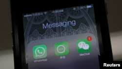 FILE - Icons of messaging applications are seen on the screen of a smart phone on this photo illustration taken in Beijing, February 24, 2014.