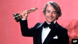 "FILE - John C. Avildsen shows off the Oscar he won for best director for ""Rocky,"" at the Academy Awards in Los Angeles, March 28, 1977. Avildsen has died at age 81."