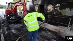 A worker of French construction group Vinci cleans near a damaged payment booth a day after the highway toll was set on fire on Dec. 18, 2018 in Bandol, near Marseille, southern France, following Yellow vests protests.