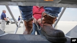 FILE - Shackled Mexican nationals, found to be in the U.S. illegally, are boarded onto a U.S. Immigration and Customs Enforcement jet for deportation, at O'Hare International Airport in Chicago, Illinois, May 25, 2010.