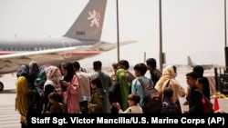 In this photo provided by the U.S. Marine Corps, civilians prepare to board a plane during an evacuation at Hamid Karzai International Airport, Kabul, Afghanistan, Wednesday, Aug. 18, 2021.
