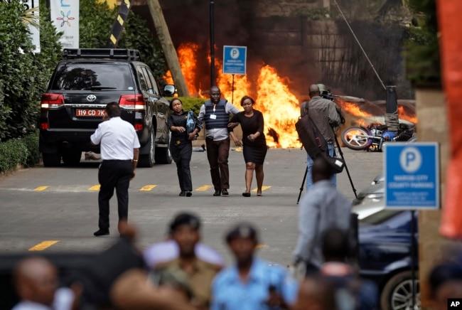 Security forces help civilians flee the scene as cars burn behind, at a hotel complex in Nairobi, Kenya, Jan. 15, 2019.