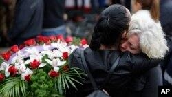 2016年8月30日意大利地震受害者集体葬礼上送葬者互相拥抱。