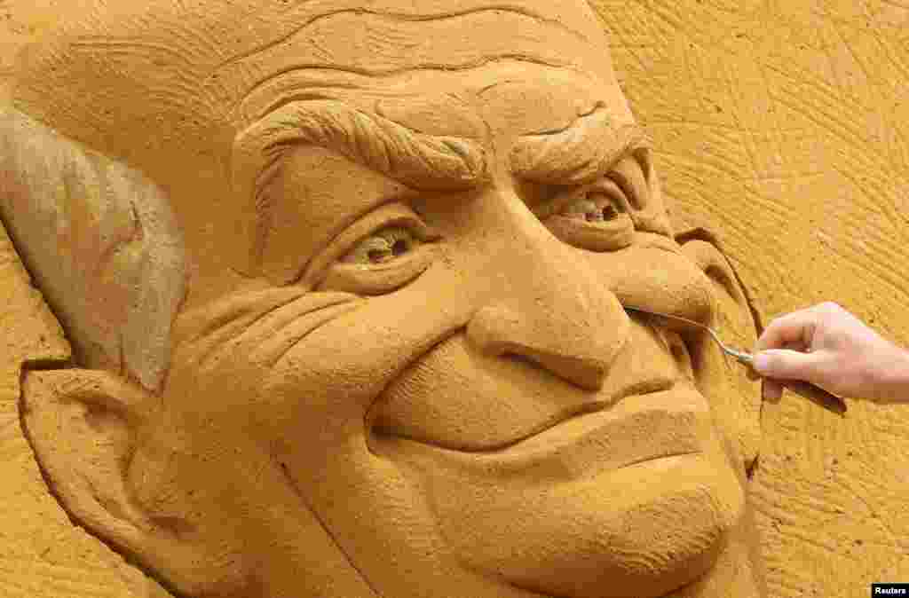 "A sand carver works on a sculpture depicting French actor Louis de Funes, during the Sand Sculpture Festival ""Dreams"" in Ostend, Belgium."