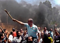Egyptians chant slogans during clashes between supporters and opponents of Egypt's president and his Muslim Brotherhood in Luxor, Egypt, June 19, 2013.