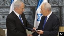 Israeli Prime Minister Benjamin Netanyahu, left, receives a folder from Israeli President Simon Peres in a brief ceremony in the president's Jerusalem residence Saturday, Feb. 2, 2013.