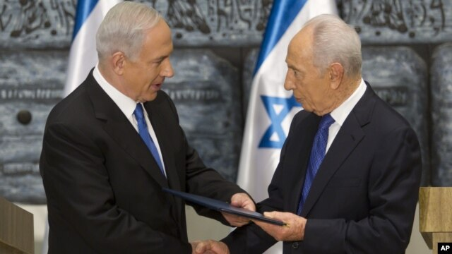 Israeli Prime Minister Benjamin Netanyahu, left, receives a folder from Israeli President Simon Peres in a brief ceremony in the president's Jerusalem residence Saturday, Feb. 2, 2013.