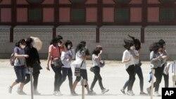Siswa-siswa SMP Korea Selatan mengenakan masker guna menghindari kemungkinan terjangkit virus MERS saat kunjungan ke istana Gyeongbok di Seoul (3/6).