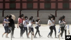 South Korean students wear masks as a precaution against Middle East Respiratory Syndrome (MERS) virus as they visit Gyeongbok Palace in Seoul, South Korea, Wednesday, June 3, 2015. (AP Photo/Ahn Young-joon)