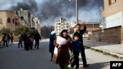A family escapes from fierce fighting between Free Syrian Army fighters and government troops in Idlib on Saturday