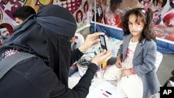 納蒂亞.阿卜杜拉在也門抗議活動中為一名女孩拍照