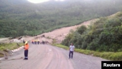 Locals inspect a landslide and damage to a road located near the township of Tabubil after an earthquake that struck Papua New Guinea's Southern Highlands, February 26, 2018. This image was supplied by a 3rd party.