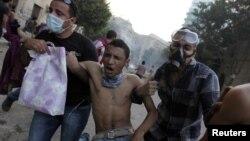 Demonstran membawa rekan mereka yang terluka dalam aksi protes di Lapangan Tahrir yang berakhir dengan bentrokan dengan petugas keamanan Mesir (foto: dok).