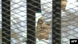 Ông Mubarak nằm trên một giường bệnh sau chiếc lồng sắt trong phòng xử án tại Học viện Cảnh sát ở Cairo, ngày 3/8/2011