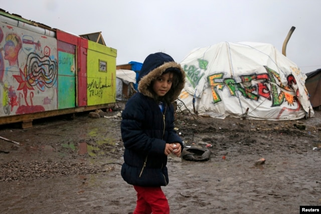 "Aida, a nine-year-old Kurdish girl, walks in the mud in the southern part of a camp for migrants called the ""jungle"" during a rainy winter day in Calais, northern France, Feb. 22, 2016."