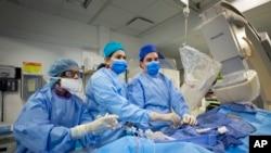 En esta foto del 16 de febrero de 2017, el Dr. Annapoorna Kini, centro, realiza una cirugía en el Hospital Mount Sinai en Nueva York.