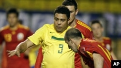 Brazil's retired striker Ronaldo (L) fights for a ball with Romania's Iasmin Latovlevici during his farewell soccer match with the Brazilian team, a friendly with Romania, in Sao Paulo, June 7, 2011