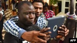 Deux participants à un atelier film avec leur smartphone le 30 mars 2019 lors de la 2ème édition du Bushman Film Festival, premier festival du film francophone d'Afrique de l'Ouest dédié au tournage sur smartphone, à Abidjan.